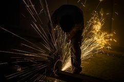 Männer an reibendem Stahl der Arbeit lizenzfreie stockfotos