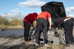 3 Männer reparieren beschädigtes Fahrzeug während des treibenden Amateurereignisses stockfoto