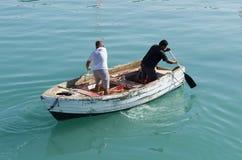 Männer rudern in der entgegengesetzten Richtung auf das Boot stockfotografie