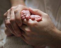 Männer ` s übergibt das Halten von neugeborenen Babyfüßen Stockbilder