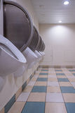 Männer ` s allgemeine Toilette mit Toiletten auf der Wand und dem karierten Boden Stockfoto