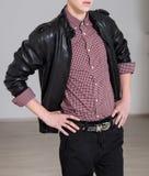 Männer ` s Art Junger moderner Mann, der schwarze Lederjacke, Denimjeans, kariertes Hemd und Gurt trägt Stockfotografie