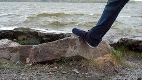 Männer ` s Beine stehen auf einem Stein vor dem See Überschwemmte Steine im Wasser Schließen Sie oben von den männlichen Füßen, d lizenzfreie stockfotografie