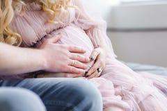 Männer ` s Hände auf dem Bauch eines schwangeren Mädchens Erwartung eines Kindes, das für Geburt sich vorbereitet Liebe des Vater stockfotografie