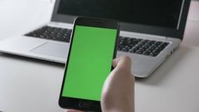 Männer ` s Hände halten eine große schwarze Smartphonehahngeste Grüner Schirm, chromakey Konzept, Laptop in den Hintergrund 60 fp stock footage
