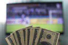 Männer ` s Hände halten Gelddollar vor dem hintergrund eines Fernsehers, auf dem Fußball spielt, Nahaufnahmen lizenzfreie stockfotografie