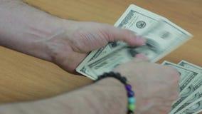 Männer ` s Hände mit einem Armband zählen die Rechnungen stock footage