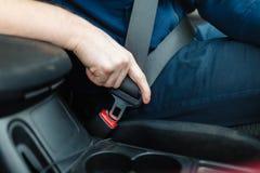 Männer ` s Hand befestigt den Sicherheitsgurt des Autos Lizenzfreie Stockfotos
