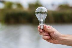 Männer ` s Hand, die Glühlampe elektrisch hält lizenzfreie stockfotografie