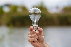 Männer ` s Hand, die Glühlampe elektrisch hält lizenzfreie stockfotos
