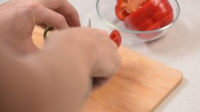 Männer ` s Hand leicht und schneidet langsam in Scheiben mit einem Messerrotgemüsepaprika stock video
