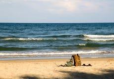 Männer ` s Rucksack und Frauen ` s Handtasche auf Sand setzen auf den Strand lizenzfreies stockbild