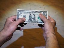 Männer ` s schmutzige Hände, die eine Dollarpapierrechnung halten Lizenzfreie Stockbilder