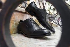 Männer ` s Schwarz-Lederabendschuhe auf den Schritten Stockfotos
