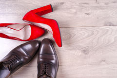 Männer ` s und die Schuhe der roten Frauen des hohen Absatzes auf weißem Hintergrund Lizenzfreie Stockbilder