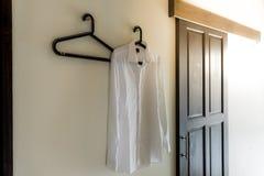Männer ` s weißes Hemd, das an der Wand mit Sonnenaufflackern hängt Stockfotos