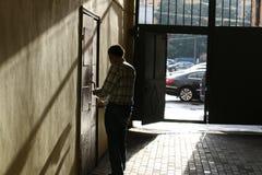 Männer schließt eine Wohnung in einem Tor ein Eisen durch einen Zaun Stockfotografie