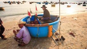 Männer sitzen im Stand am runden Fischerboot auf Strand in Vietnam stock video