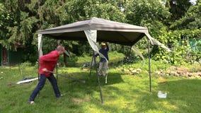 Männer stabilisieren Metallrohre zum Laubenrahmen mit Segeltuch vom Regen Stockfotografie
