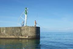 Männer tun Fischen vom Pier in Schlucht-Heilig-Gilles-De Réunion, Frankreich Lizenzfreies Stockfoto