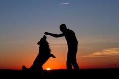Männer u. Hundeschattenbild lizenzfreie stockfotografie