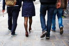 Männer und eine Frau, die auf den Bürgersteig geht Stockbild