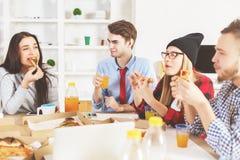 Männer und Frauen, die am Arbeitsplatz essen stockbild