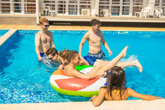 Männer und Frauen, die im Pool mit Schwimmenkreisen spielen Lizenzfreie Stockbilder