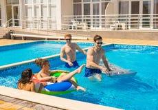 Männer und Frauen, die im Pool mit Schwimmenkreisen spielen Stockbild
