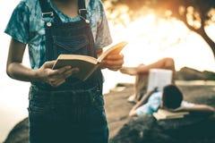 Männer und Frauen lasen Bücher in der ruhigen Natur stockfotografie