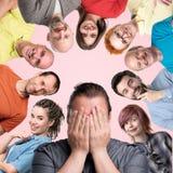 Männer und Frauen, welche die positiven lächelnden und lachenden Gefühle zeigen Mann, der sein Gesicht schließt Scheinkonzept stockfoto
