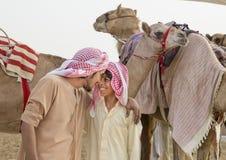 Männer und Kamele im Unebenheitsal Khali Desert am leeren Viertel, in A Lizenzfreies Stockfoto