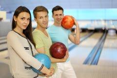 Männer und Mädchen lächeln und halten Kugeln im Bowlingspielklumpen an stockbild