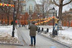 Männer verzieren mit bunten Flaggen in der Park-Einsiedlerei für den Feiertag in Moskau Stockbilder