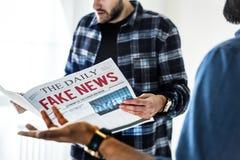 Männer, welche die Zeitung lokalisiert auf weißem Hintergrund lesen stockbild