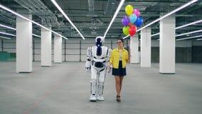 Människa-som cyborg går med en flicka som rymmer ballonger stock video
