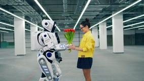 Människa-som cyborg ger tulpan till en kvinna stock video