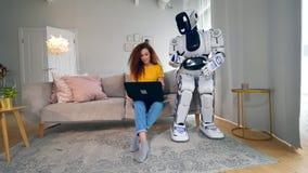 Människa-som cyborg håller ögonen på en dam att arbeta på en bärbar dator stock video