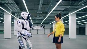 Människa-som cyborg tar en flickas hand stock video