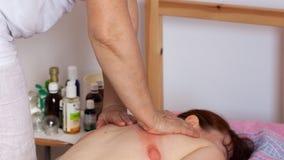 Människabaksida som mottar vakuumet som kuper massage Arkivbilder
