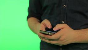 Människahänder med telefonen på den gröna skärmen stock video