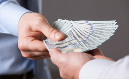 Människahänder som utbyter pengar på blå bakgrund royaltyfri foto