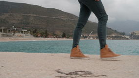 Människan i riven sönder jeans och orange gymnastikskor är på sandkusten lager videofilmer