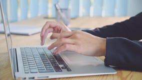 Människan räcker arbete på bärbara datorn på kontorsbakgrund En ung kvinna i kontorsvisartavlorna ett dokument på tangentbordet stock video