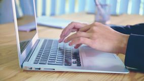Människan räcker arbete på bärbara datorn på kontorsbakgrund En ung kvinna i kontorsvisartavlorna ett dokument på tangentbordet lager videofilmer