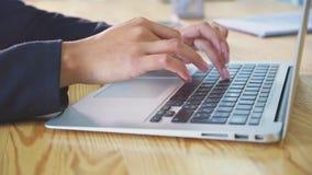 Människan räcker arbete på bärbara datorn på kontorsbakgrund En ung kvinna i kontorsvisartavlorna ett dokument på tangentbordet arkivfilmer