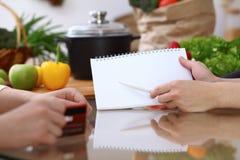 Människan räcker att peka in i anmärkningsboken med kopieringsutrymmeområde Danandemeny för två kvinna i köket, closeup laga mat  arkivfoto