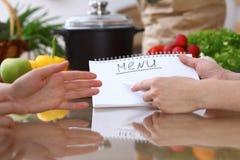 Människan räcker att peka in i anmärkningsboken med kopieringsutrymmeområde Danandemeny för två kvinna i köket, closeup laga mat  fotografering för bildbyråer