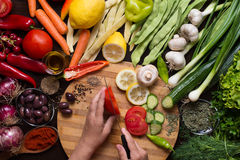 Människan räcker att skiva grönsaker och variation av grönsaker och kryddor omkring Royaltyfri Fotografi
