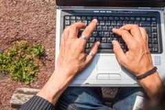 Människan räcker att skriva en bärbar dator Royaltyfri Bild
